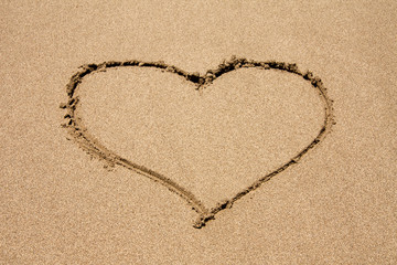 heart symbol drawn in the sand on a beach with wave. Valentine's