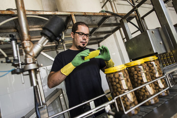 Man in factory taking smartphone picture at conveyor belt with filled olive glasses