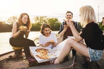 Friends sitting together outdoors sharing a pizza