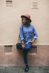 Portrait of smiling young woman wearing hat and denim shirt standing in front of house facade