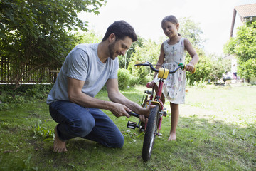 Father inflating daughter's bicycle