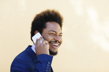 Portrait of smiling young businessman telephoning with smartphone