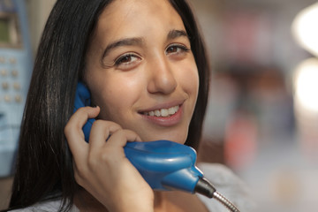 Young girl talking on a pay phone