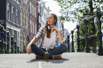Netherlands, Amsterdam, young woman sitting with headphones and beer bottle on bridge