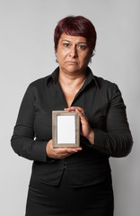 Unhappy middle aged woman holding photo frame