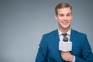 Smiling newsman holding a microphone.