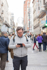 Young man with glasses in looking his mobile device in an addictive way in a busy street