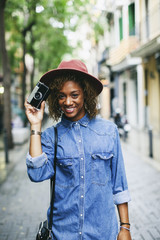 Spain, Barcelona, portrait of smiling young woman wearing hat and denim shirt holding camera