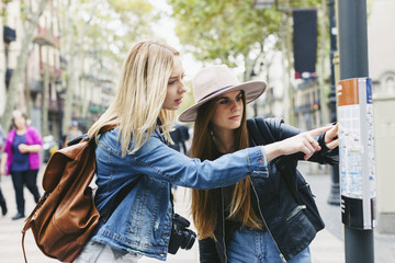 Spain, Barcelona, two young women looking at city map on pole