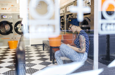 Tattooed young woman hearing music with earphones in a launderette