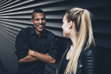 Black dressed young man face to face with young woman in front of black facade