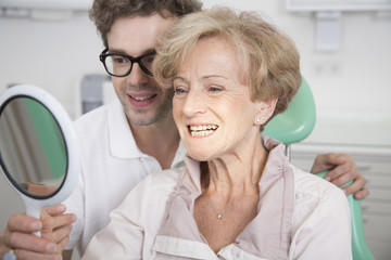 Senior woman in dentist's chair checking her teeth in mirror