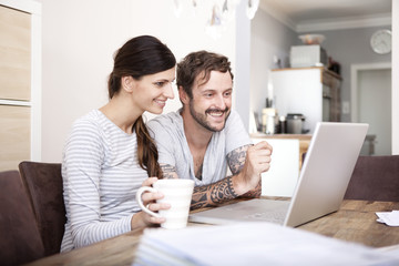 Smiling couple sitting at wooden table looking at laptop