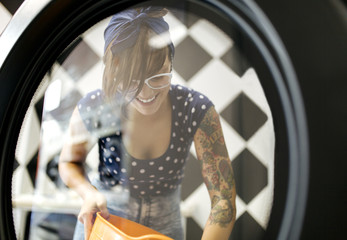 Portrait of tattooed young woman in a launderette