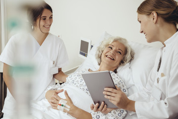 Senior woman in hospital talking to doctor and nurse