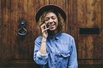Spain, Barcelona, portrait of smiling young woman telephoning in front of wooden door