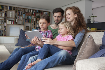 Couple sitting with their with two little daughters on couch in the living room looking at digital tablet