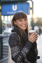 Germany, Berlin, portrait of happy young woman with coffee to go