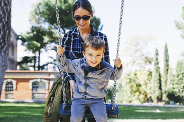 Mother pushing son on a swing at the playground