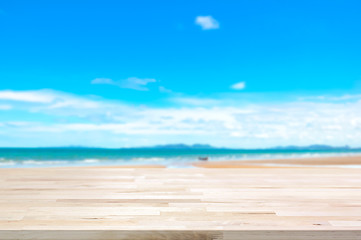 Wood table top on blur summer beach background
