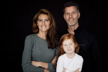Portrait of smiling couple with little daughter in front of black background