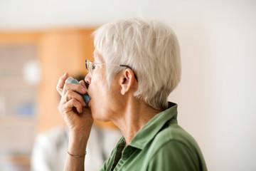 White haired senior woman using inhaler