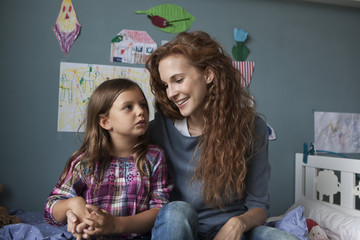 Portrait of woman with her little daughter in children's room