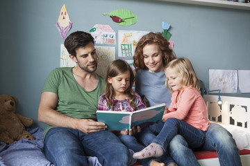 Couple and little daughters sitting together on bed in children's room reading a book
