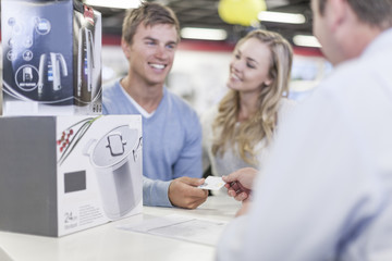 Young couple at counter in shop paying for purchase