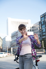 Germany, Berlin, young woman taking a picture with her smartphone