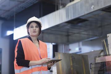 Female engineer using a digital tablet in an industrial plant, Freiburg Im Breisgau, Baden-Württemberg, Germany
