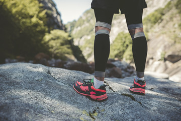 Ultra runner in mountains standing on rock