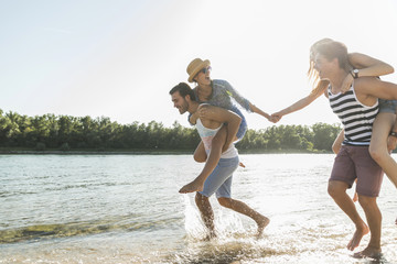 Two playful young couples at the river