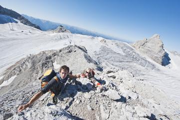 Austria, Steiermark, Dachstein, Young couple climbing rock