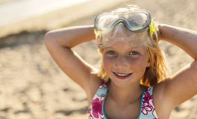 Portrait of smiling blond little girl with diving mask and hands behind her head on the beach