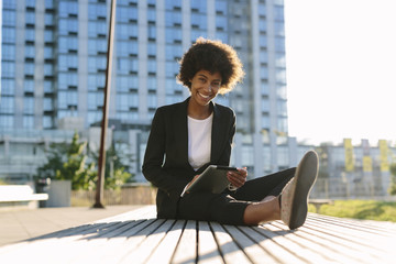 USA, New York City, portrait of businesswoman sitting on a bench with digital tablet