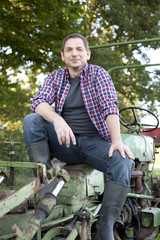Germany, Saxony, Mature man sitting on tractor, smiling, portrait
