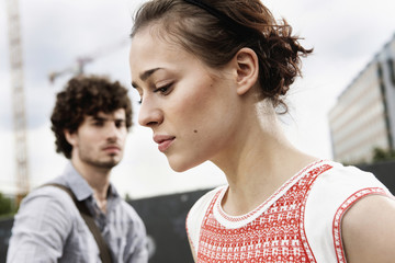 Germany, Berlin, Young couple, woman looking down, side view, portrait, close up