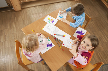 Germany, Children in nursery sitting at table drawing pictures, elevated view