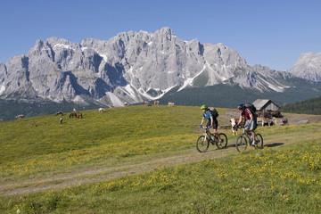 Italy, Dolomites, Couple mountainbiking