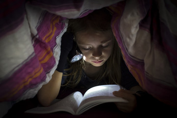 Little girl with torch reading book under a blanket