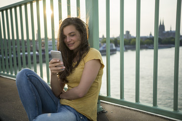Germany, Cologne, young woman sitting on Rhine bridge looking at her smartphone