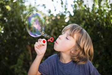Blond little boy blowing soap bubbles