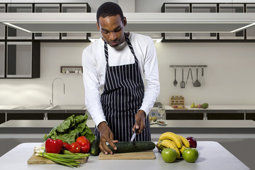 African American male chef wearing an apron in a home or restaurant kitchen