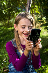 Happy little girl looking at smartphone in a garden