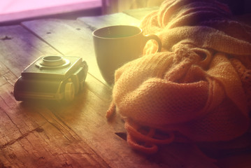 selective focus photo of pink cozy knitted scarf with to cup of coffee next to old photo camera on a wooden table. photographed without editing software, using handmade filter