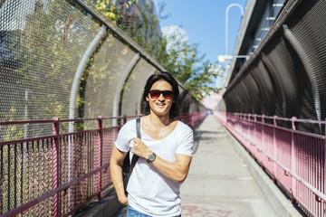 USA, New York City, smiling man on Williamsburg Bridge in Brooklyn