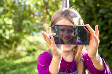 Little girl sitting on a meadow in the garden showing display of smartphone with her selfie