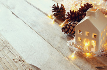 pine cones and decorative wooden house next to gold garland lights on wooden background. copy space