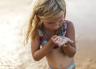 Little girl on the beach with an elver on her hand